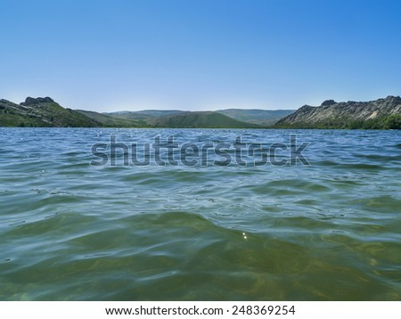 Beautiful lake in the mountains on a sunny day - stock photo