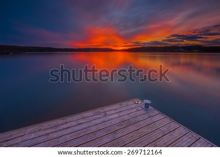 Beautiful lake landscape with vibrant sunset and pier. Long exposure landscape. - stock photo