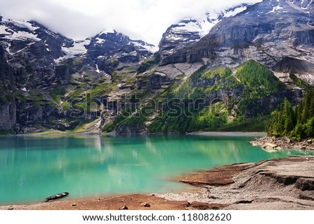 Beautiful lake Oeschinensee with emerald green water in the heart of Swiss Alps, Kandersteg, Switzerland - stock photo