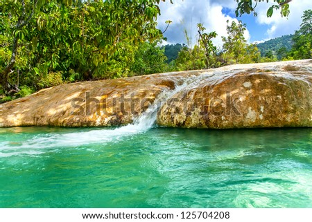 Beautiful lake with crystal clear water and a waterfall. Emerald pool. - stock photo