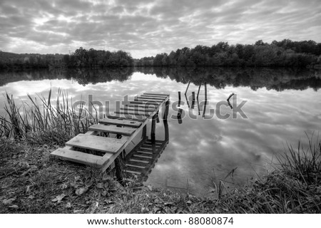 Beautiful lake with pier on cloudy day  in black and white - stock photo