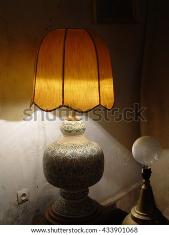 Beautiful lamp with the lamp shade about an old wall. Evening twilight