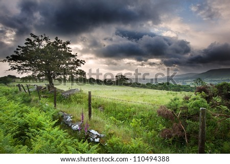 Beautiful landscape across countryside to mountains in distance with moody sky - stock photo
