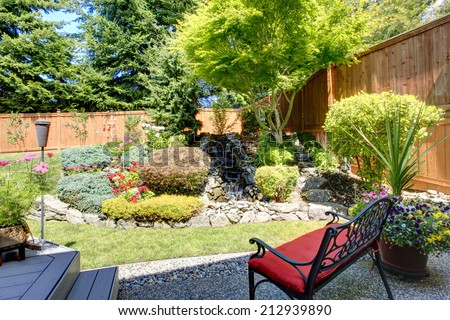 Beautiful landscape design for backyard garden with small bench - stock photo