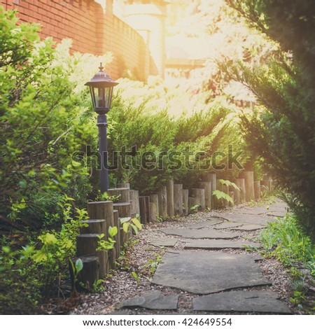 Beautiful landscape design, garden path tiles closeup with park light, wooden fence, evergreen bushes and shrubs in sunlight. Modern landscaping. Summer garden or park design. - stock photo