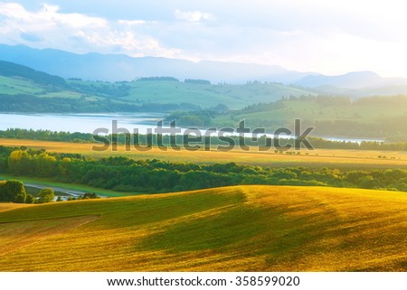 Beautiful landscape, green and yellow meadow and lake with mountain in background. Slovakia, Central Europe.