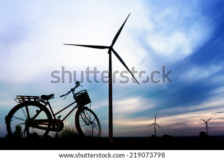 beautiful landscape image with bicycle and Windturbine farm at the sunrise - stock photo