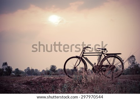 beautiful landscape image with Bicycle at sunset;vintage color tone style - stock photo
