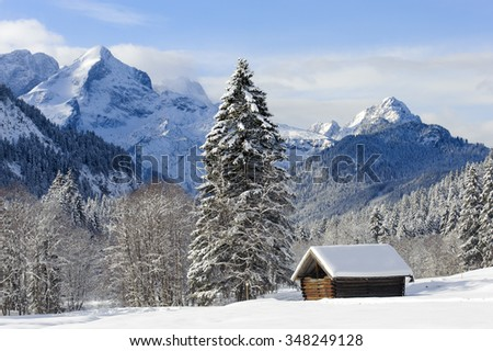 beautiful landscape in Bavaria with alps mountains in snow with little wooden hut - stock photo