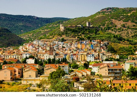 Beautiful landscape in Bosa with green hills, colorful houses of the district Sa Costa and and the Castle - il Castello di Serravalle, also called il Castellos di Malaspina in Sardinia, Italy.