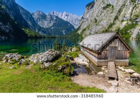 Beautiful landscape of alpine lake with crystal clear green water and mountains in background, Obersee, Germany - stock photo