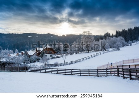 Beautiful landscape of Alpine town in mountains covered in snow - stock photo