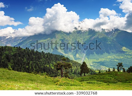 Beautiful landscape of Caucasus mountains. Snow-capped peaks and green valley below. Blue sky with clouds above - stock photo