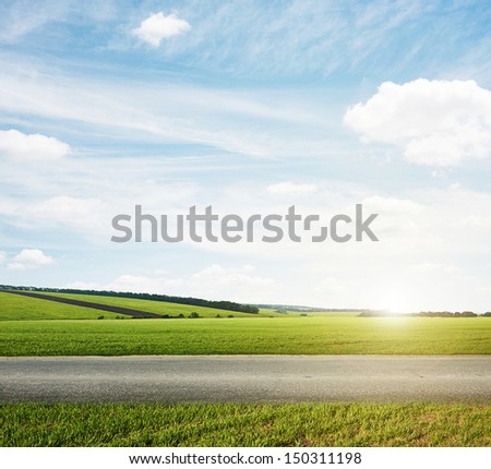 beautiful landscape of green meadow and road - stock photo