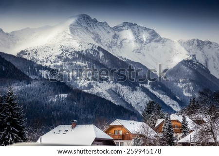 Beautiful landscape of high Austrian Alps with traditional houses covered by snow - stock photo