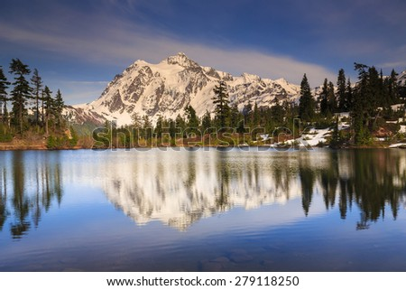 Beautiful landscape of snowy mountains reflecting at the lake - stock photo