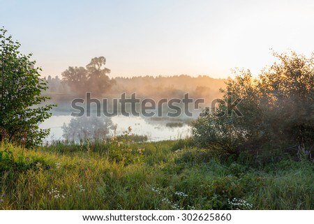 Beautiful landscape of sunrise over the river on a foggy morning - stock photo