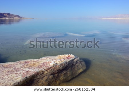 Beautiful landscape of the Dead Sea coastline with a big stone covered the crystal of salt in summer morning - stock photo