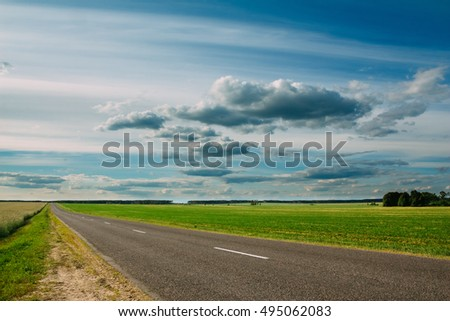 Beautiful landscape of the road and green summer field with a background of sky and clouds