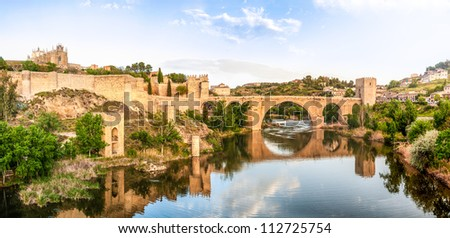 Beautiful landscape of Toledo in Spain. Stone bridge across calm river. Blue sky reflected in crystal clear water. Big fort and country houses in background. Popular tourist place in Europe. - stock photo