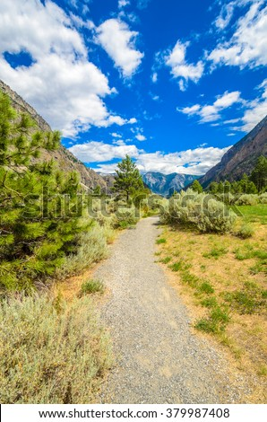 Beautiful landscape of valley in Alpine mountains, small trail, hike root, majestic picturesque view in sunny day. Lillooet Seton Lake. Vancouver. British Columbia. Canada. - stock photo