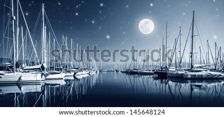 Beautiful landscape of yacht harbor at night, full moon, marina in bright moonlight, luxury water transport in nighttime, vacation concept  - stock photo