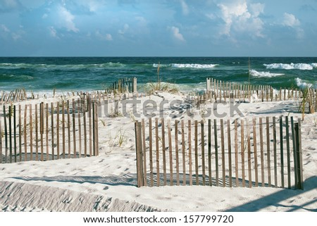 Beautiful landscape or seascape of white sand beaches, puffy clouds, cheerful sand fences and emerald tropical waves with frothy breakers on a sunny day at Pensacola, Florida beach.  - stock photo