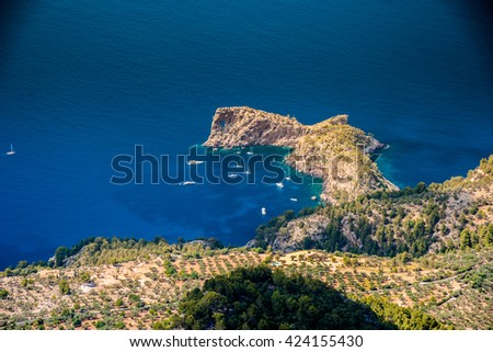 Beautiful landscape picture with rocky mountains and sailboats near the ring-shaped cliff, Mallorca, Spain. - stock photo