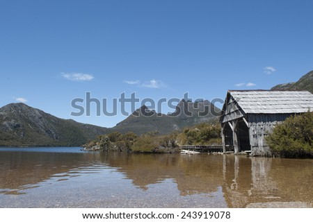 Beautiful landscape scenery of Cradle Mountain National Park in Tasmania, Australia, with clear water of Dove Lake and historic boat shed, blue sky as copy space. - stock photo