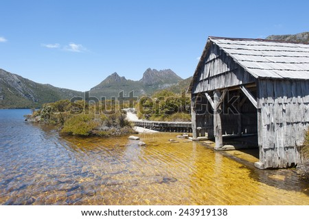 Beautiful landscape scenery of Cradle Mountain National Park in Tasmania, Australia, with Dove Lake and historic boat shed, blue sky as copy space. - stock photo