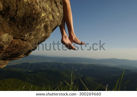 Beautiful landscape view from high mountaing on green hills with wood and human female legs barefoot of girl sitting on rock on natural blue sky copyspace background, horizontal picturepicture - stock photo