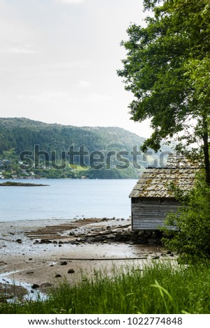 Beautiful landscape view of old norwegian cottage by lake coast and forest, water mirror reflecting on sunny day.