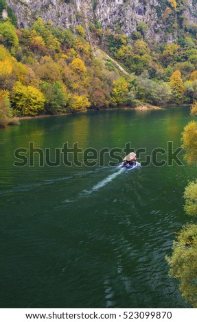 Beautiful landscape view with boat on the river and colorful autumn forest