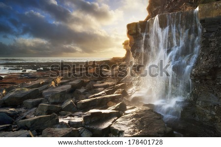Beautiful landscape waterfall flowing into rocks on beach at sunset - stock photo