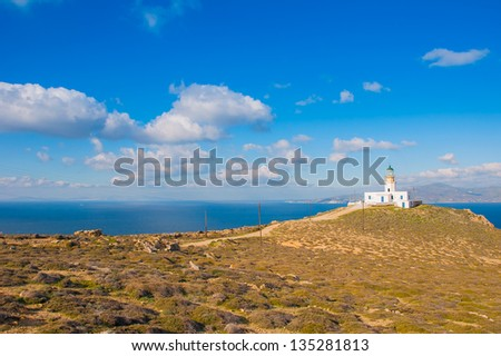 Beautiful landscape with a lighthouse, sea and blue sky with clouds.