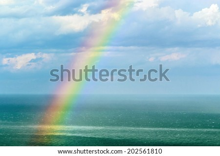 beautiful landscape with a rainbow after the rain. focus on the waves in front of the frame and rainbow - stock photo