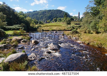 Beautiful landscape with a small river and the Round Tower at Glendalough in Wicklow Mountains