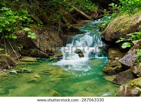 Beautiful landscape with a small waterfall in the forest - stock photo