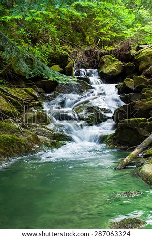 Beautiful landscape with a waterfall in the forest - stock photo