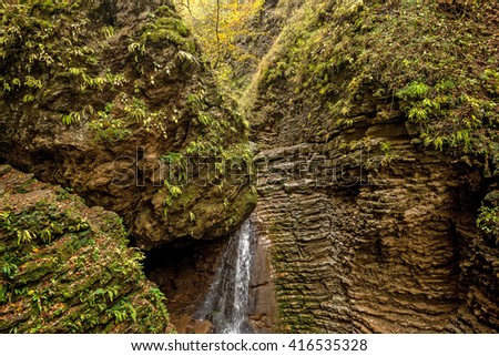 Beautiful landscape with forest waterfall and lush foliage in autumn - stock photo