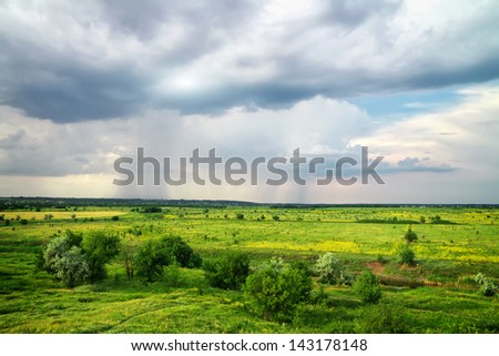Beautiful landscape with green fields and cloudy rainy sky - stock photo