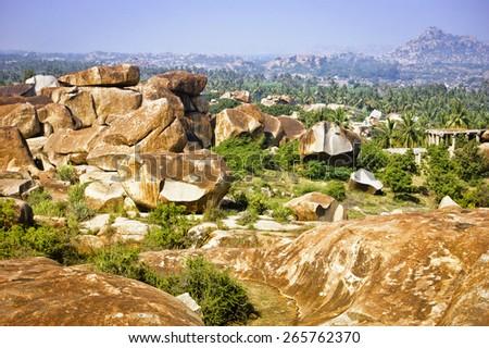 Beautiful landscape with large steep rocks, palm trees and bushes near Hampi, India - stock photo