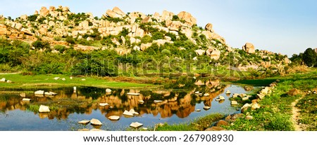 Beautiful landscape with large steep rocks, trees and bushes near Hampi, India. - stock photo
