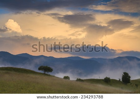 Beautiful landscape with mountain and trees under an amazing dawn sky. Carpathian Mountains. Ukraine.