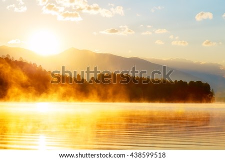 beautiful landscape with mountains and lake at dawn in golden blue and orange tones - stock photo