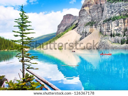 Beautiful landscape with Rocky Mountains and tourists canoeing on azure mountain lake, Alberta, Canada - stock photo