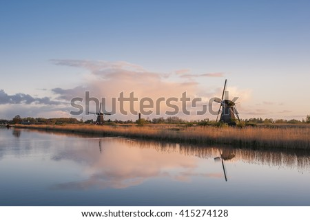 Beautiful landscape with windmills and majestic sky reflection in water - stock photo