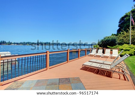 Beautiful large deck near the lake with  chairs and landscape. - stock photo