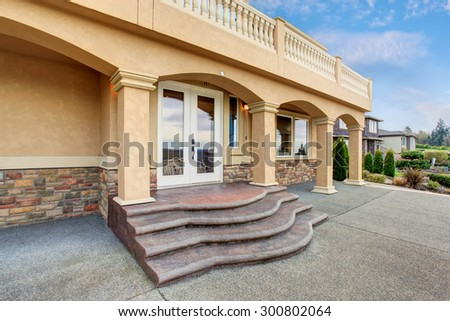 Beautiful large home with beamed balcony and big walkway. - stock photo