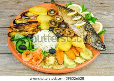 Beautiful large mackerel on a plate full of vegetables and salad